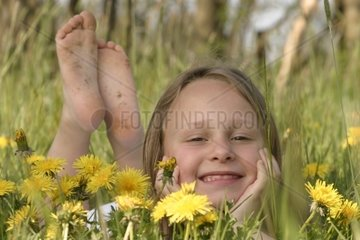 Smiling Girl lying in Meadow with Dandelion