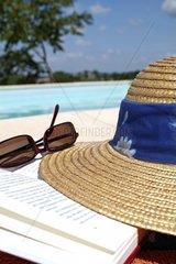 Strohhut  Sonnenbrille und Buch am Pool