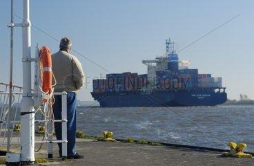 Mann schaut auf Containerfrachter auf Elbe hinaus  Hamburg  Germany