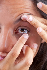 View of a woman's brown eye while inserting a contact lens