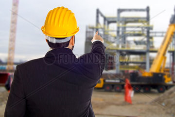Businessman with construction helmet isolated on the job site