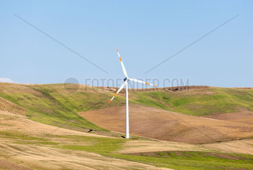 Wind turbines in operation in the summer with blue sky