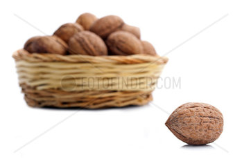 Wicker basket with walnuts isolated on a white background