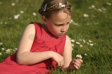 Girl in Meadow playing with Daisies