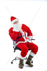 Young Santa Claus sitting on an office chair on white background