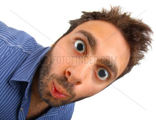 Young boy with a surprised expression with dilatated pupils on white background