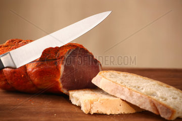 Italian capocollo with bread on beige background