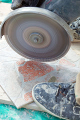 A man cutting a floor tiles with a grinder