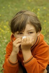 Allergic Child on Flower Meadow with Tissue