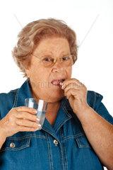 Elderly woman taking medicine on white background