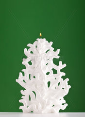 Christmas candle shaped like a Christmas tree on green background