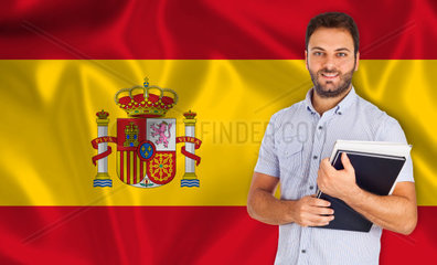 Young male student smiling over Spanish flag