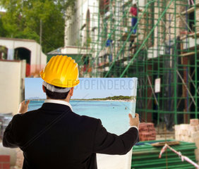Businessman dreams vacation on the job site