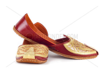 Pair of traditional Indian shoes on white background