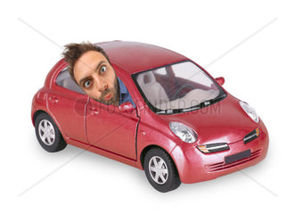 Young boy with a surprised expression in the red car