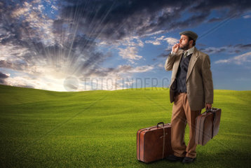 Emigrant man with the suitcases in the field