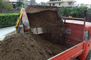Excavator loading ground in truck tipper in the garden