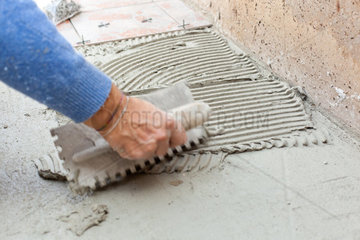Tiler works with flooring in the backyard