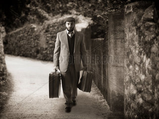 Emigrant man with the suitcases in a narrow country