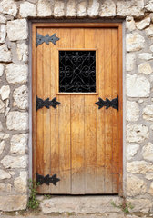 Old wooden door in the stone wall