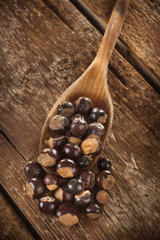 Guarana seeds on wooden table photographed with studio lighting
