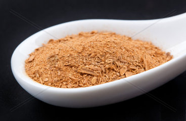 Cinnamon Powder in white spoon on black table