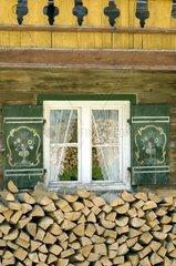 Bauernhaus mit Holzscheiten vor dem Fenster