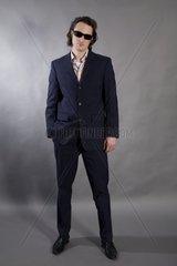 Mann mit Sonnenbrille in dunkelblauem Anzug  stehend