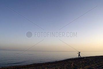 Spaziergaenger schmeisst Steine ins Meer