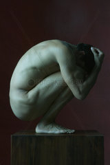 Nude man crouching in fetal position  head in hands  side view