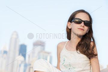 Preteen girl relaxing outdoors  wearing sunglasses