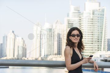 Woman leaning against railing with smarphone in hand  skyscrapers in background