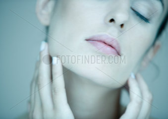 Woman touching face  eyes closed  portrait  partial view