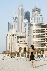 Woman walking on beach with skyscrapers in background  Dubai  United Arab Emirates