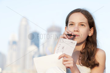 Preteen girl sitting outdoors with pen in mouth  looking up in thought
