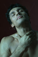 Barechested man with hand on throat  eyes closed