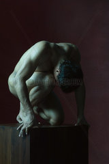 Nude man crouching  head down