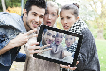 Friends photographing themselves with digital tablet outdoors