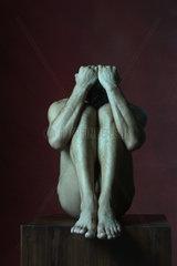 Nude man sitting in fetal position  head down