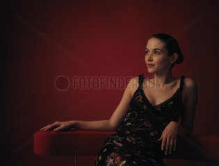 Woman wearing dress  sitting in chair  looking away