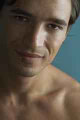 Barechested man looking at camera smiling  close-up