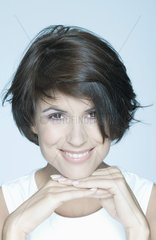Woman with short hair  hands under chin  smiling  portrait