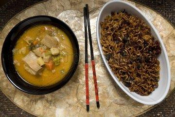 asiatische Gemuese Fisch Suppe und gebratene Nudeln in Schaelchen mit Essstaebchen