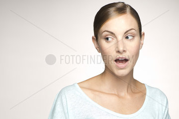 Young woman looking away with mouth open in surprise  portrait
