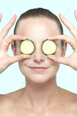 Woman holding cucumber slices on eyes