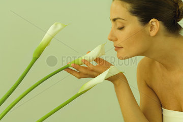 Young woman smelling calla lilies