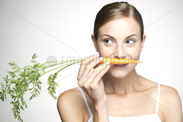 Young woman smelling carrot