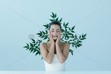 Young woman with hands on cheeks  eyes closed  leafy pattern in background