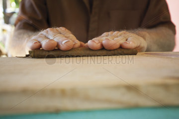 Man's hands crafting a cigar