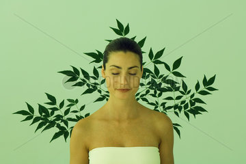 Young woman with eyes closed  leaf pattern in background